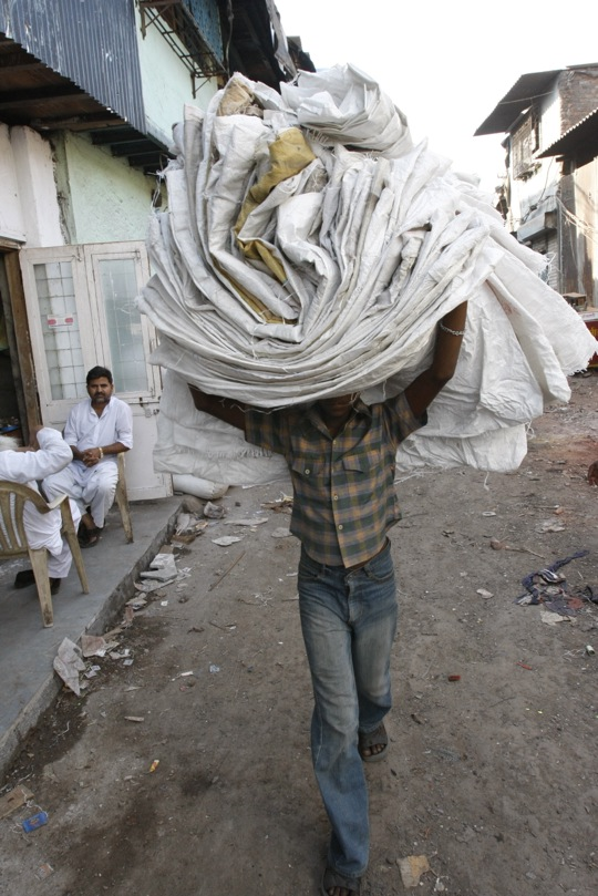 man carrying recycled bags