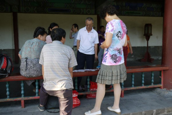 locals relaxing in the park playing a traditional chinese tile game